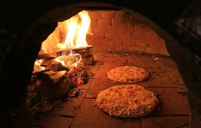 Pizzas Topped with Cheese and Tomato Being Baked in the Wood Fired Oven