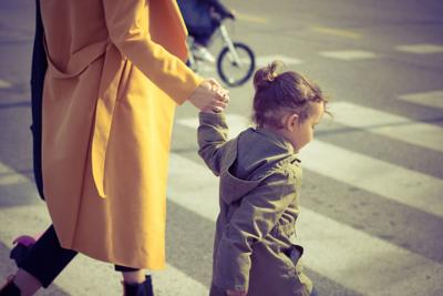 Little girl crossing the street with mother. Safety Town