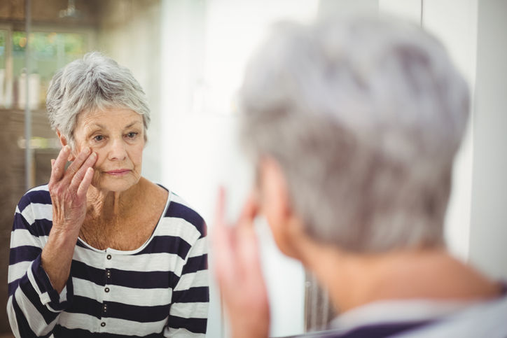 Reflection of senior woman looking at skin in mirror wrinkles