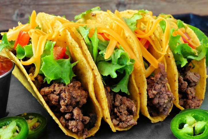 Group of ground beef hard shelled tacos close up