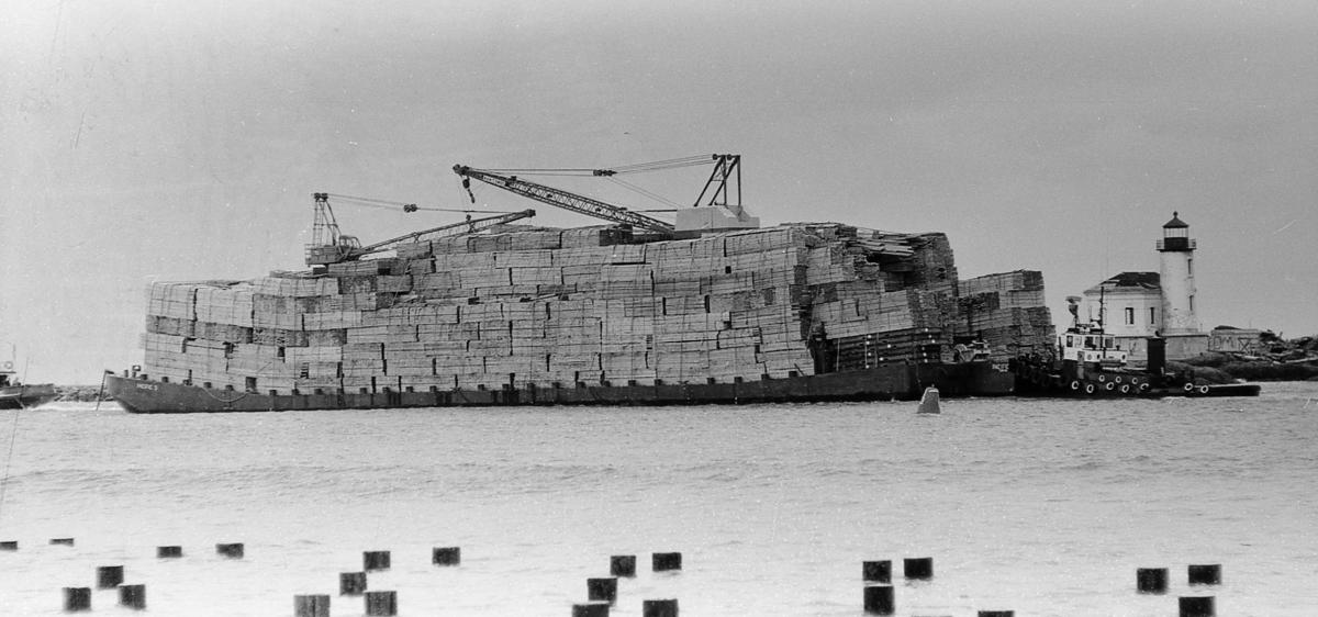 Barge Pacific 3 passes lighthouse on its way to sea with largest load of lumber ever to leave port, March, 1962