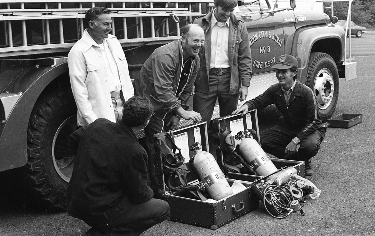 Bill Donahue, Bill Pullen, Jack McMahon, Barry Winters, Lanny Boston look at new air masks for fire dept. 7/75