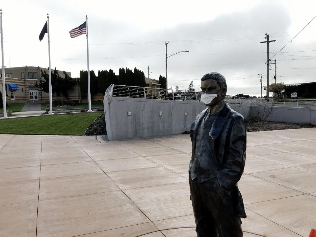 Statute of North Bend founder Louis Simpson wearing mask