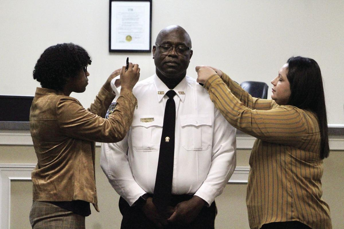 Carter Hyman and Laura Starnes put on Steve Hyman's epaulettes, signifying hisrank as chief at the ceremony on Jan. 9.