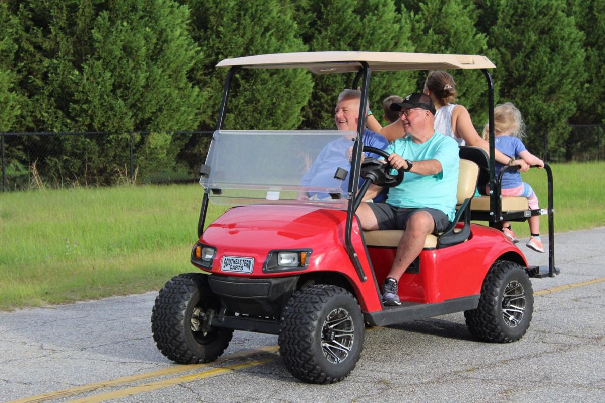 Pastor Fred Evers, left, rides on a golf cart as the pace car in the evening during the 5K charity race.