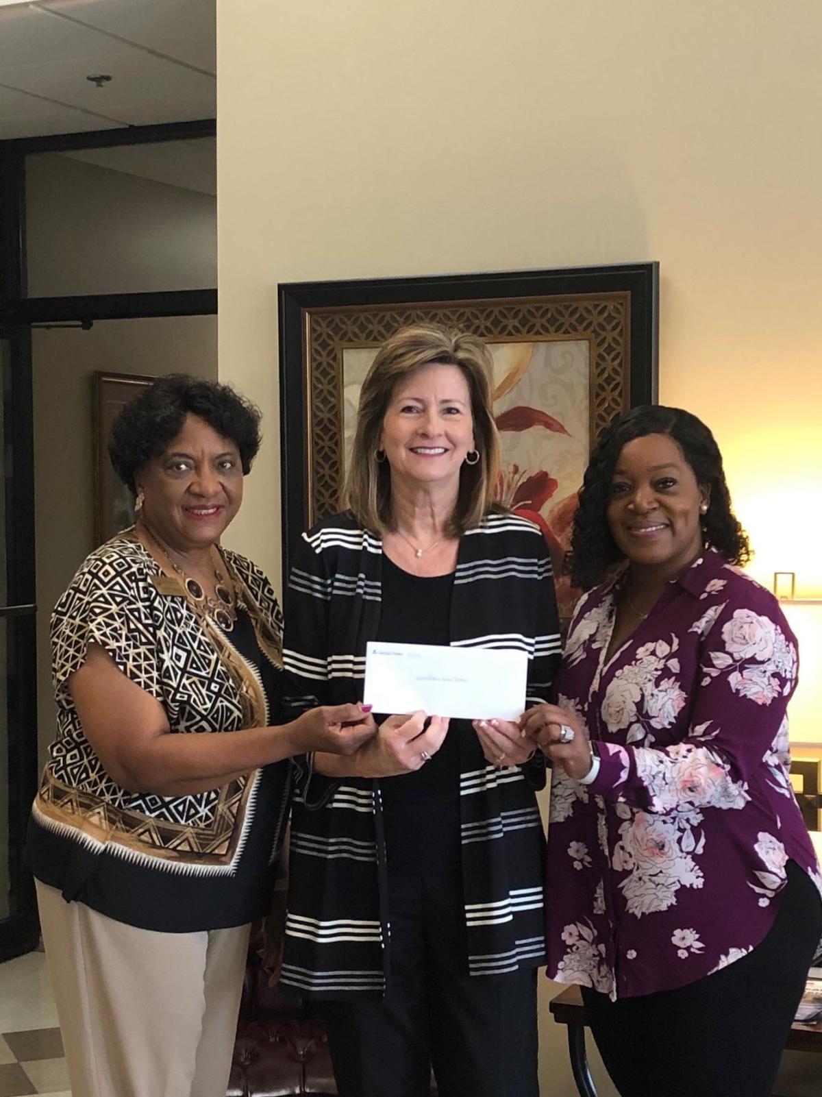 Georgia Power area manager Lynn Lovett presents a donation to the Leroy Rogers Senior Center staff. Left to right: Fran Kinchen (executive director), Lynn Lovett of Georgia Power, and Natasha Patrick (nutrition coordinator).
