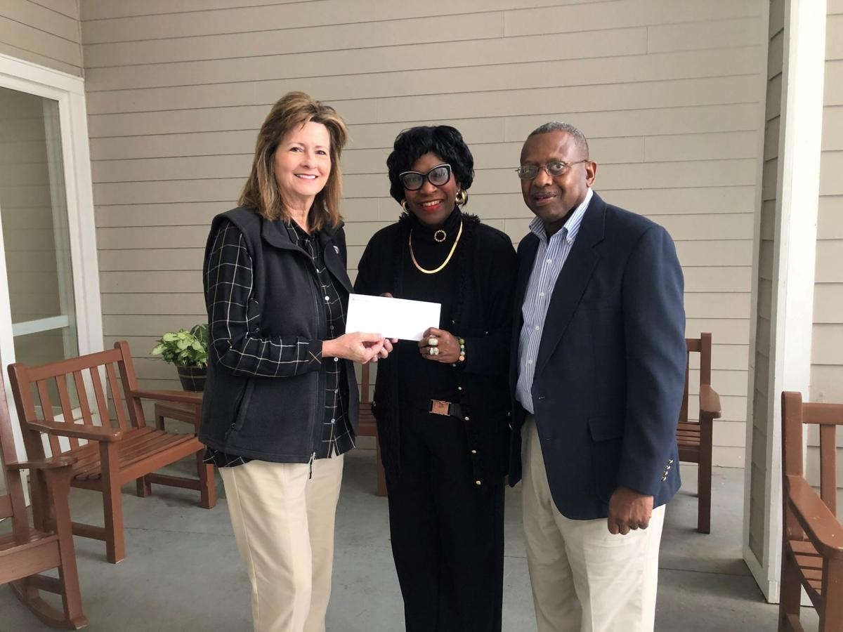 Georgia Power area manager Lynn Lovett presents donation to Joyce and Larry Mims, founders of Mims Kids.