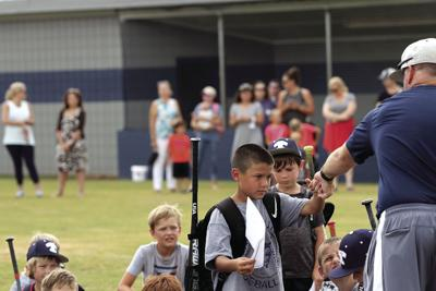 Eli Gomez fist bumps Tift County head baseball coach Kyle Kirk after winning the Most Valuable Player award for his age group at camp.