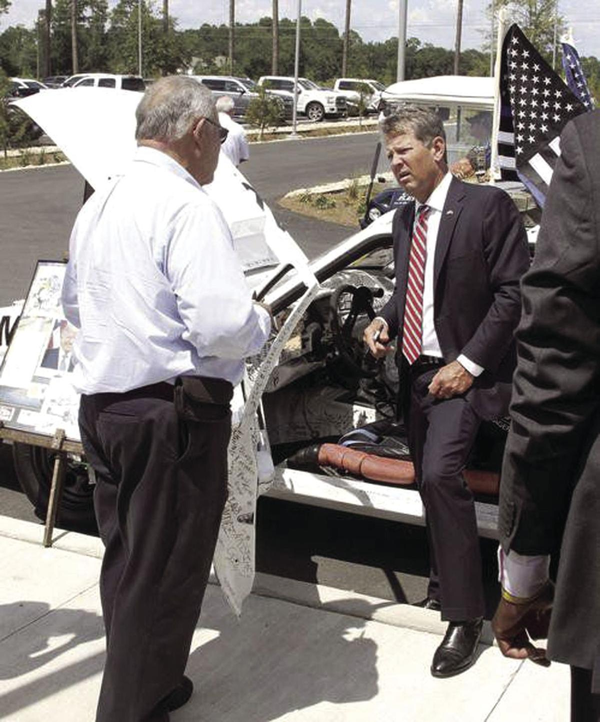 Gov. Brian Kemp prepares to sign Mike Fuches' law-enforcement tribute car outside the Philadelphia College of Osteopathic Medicine's South Georgia campus Tuesday.