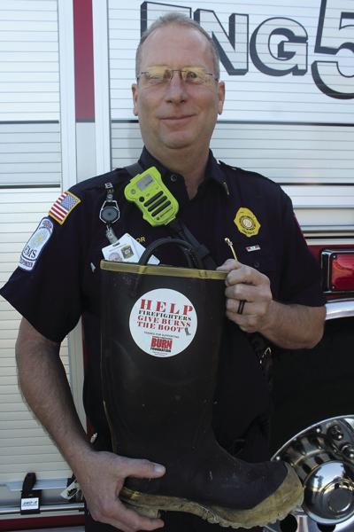 Lieutenant Jay Taylor holding one of the boots that will be used for collecting donations.