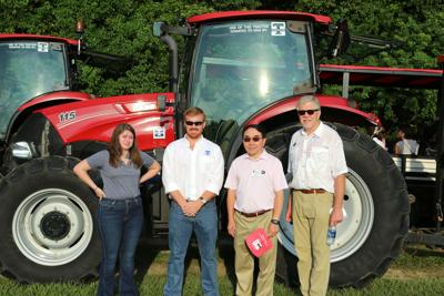 Tidewater representatives, UGA Provost S. Jack Hu and  University of Georgia-Tifton Assistant Dean Joe West in front of one of the tractors donated to UGA-Tifton this fall.