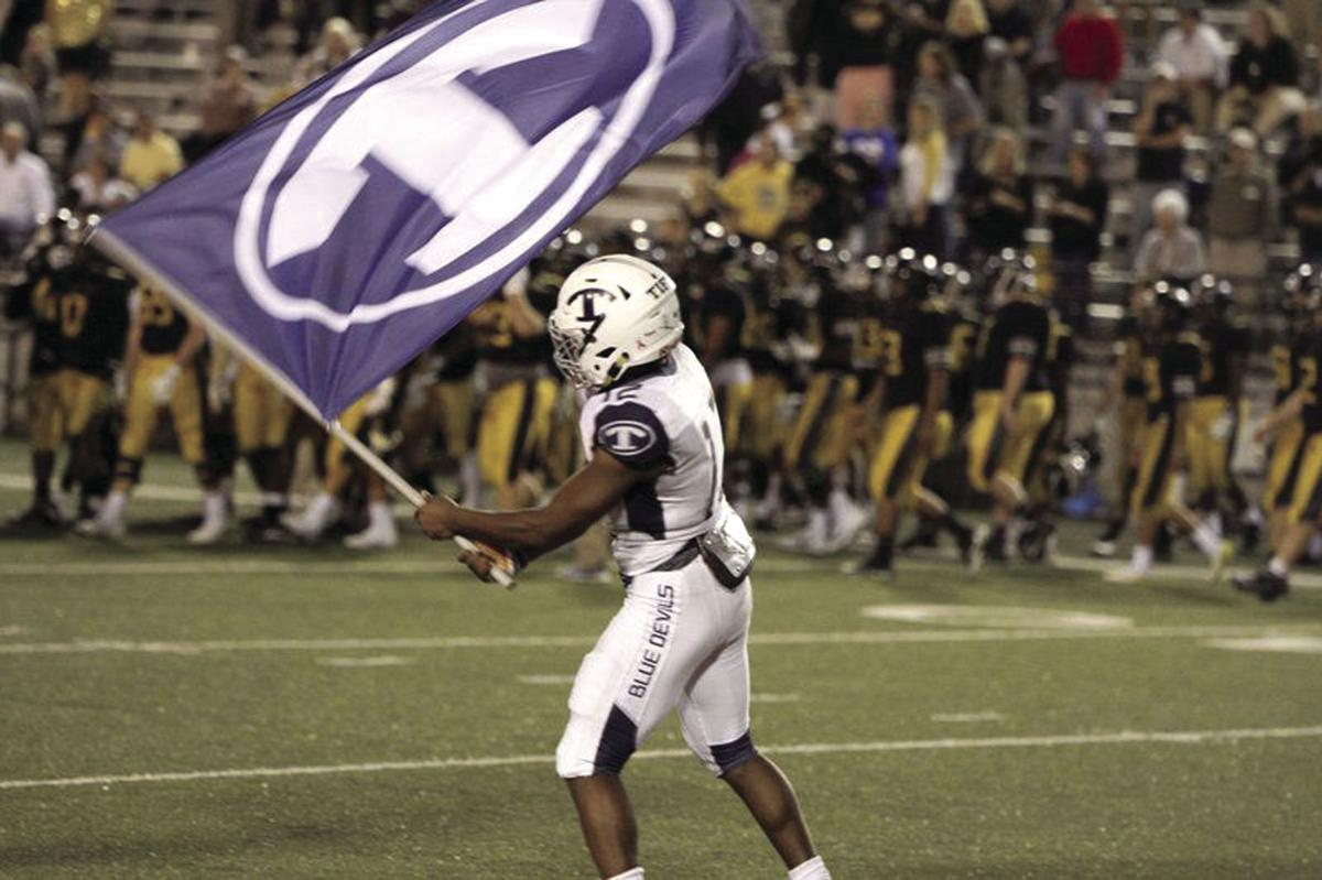 Cam Cobb waves the Tift County flag after the Blue Devils upset Colquitt County, 38-35, in 2017.