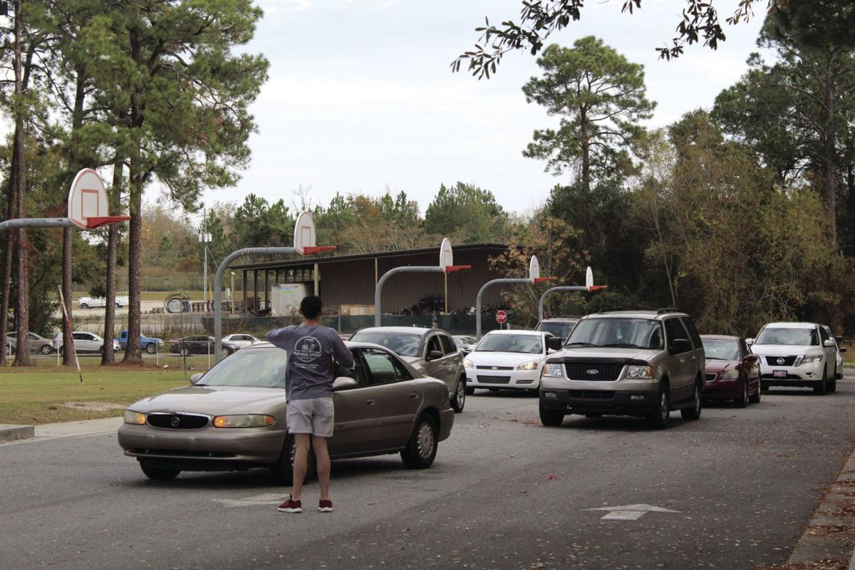 Cars lined up around Charles Spencer Elementary School four hours early to receive a bag of food before Thanksgiving.