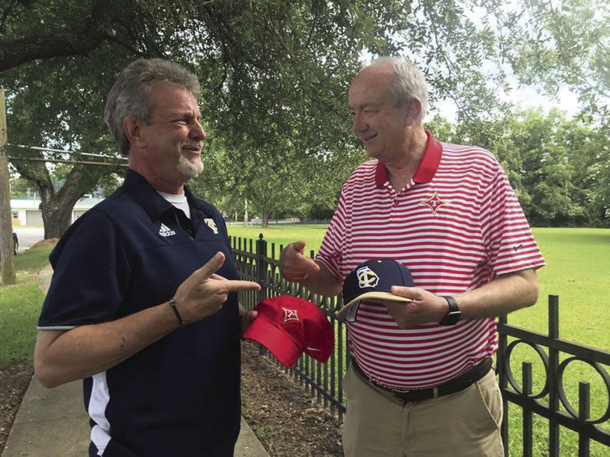 Randy Young and Darrell Allen, Thomasville-area play-by-play high school football commentators, realize they have mistakenly swapped caps.