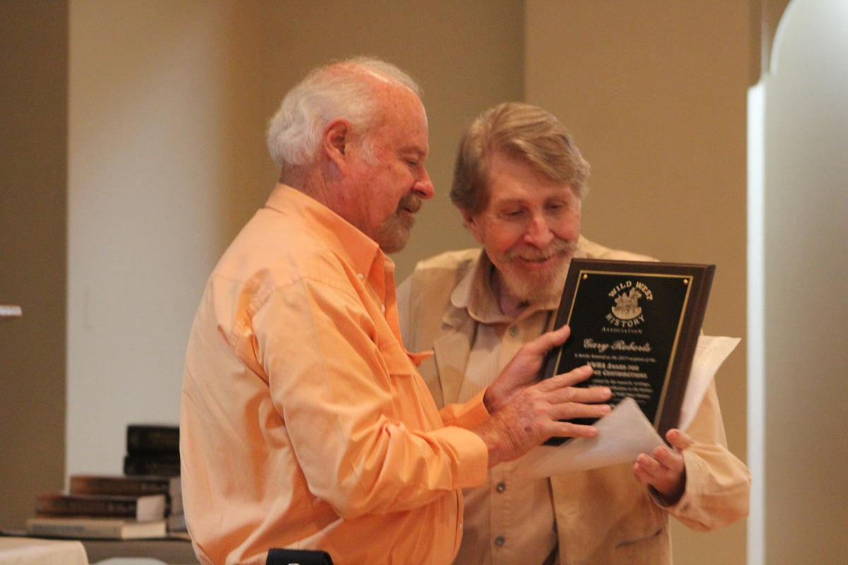 Eddie Lanham presents Gary Roberts with the award for lifetime achievement in the field of Wild West history.