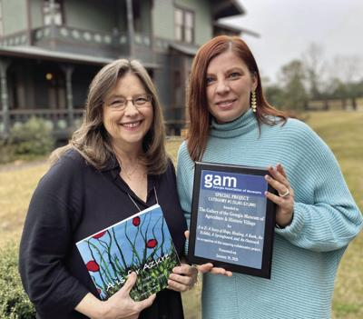 "Donna Falcone (left) and Polly Huff with the GAM award for ""A to Z."""