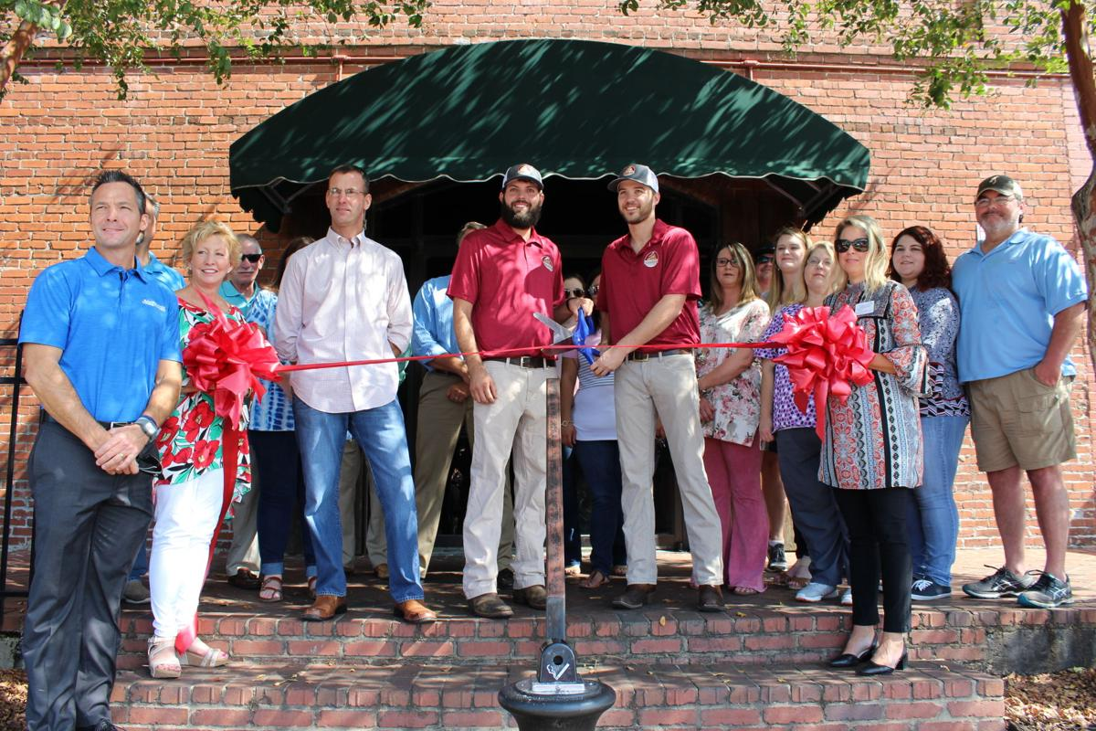 Casey Denny and Sonny Blevins, center, cut the ribbon to open Terminal South on Friday, Sept. 21.