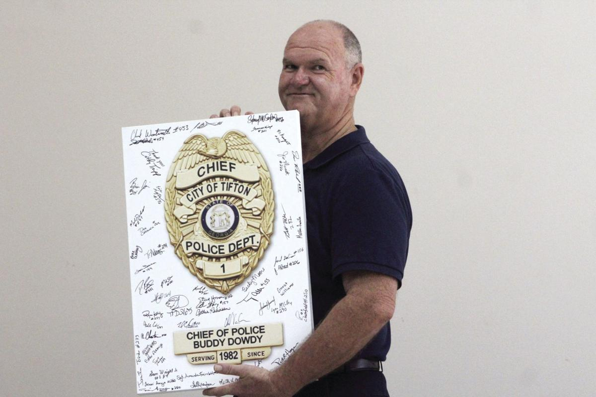 Retired Police Chief Buddy Dowdy holds up a canvas covered with signatures from everyone at the Tifton Police Department.