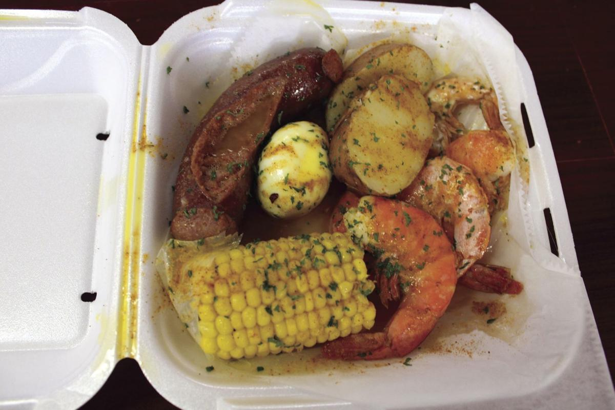 A signature dish from Tonyo's Seafood restaurant with sausage, jumbo shrimp, corn on the cob, roasted potatoes and a boiled egg with garlic seasoning all over it.