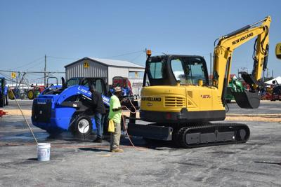 Two New Holland Agriculture employees wash the company's vehicles Friday in preparation for browsers to come during the Sunbelt Expo this week.