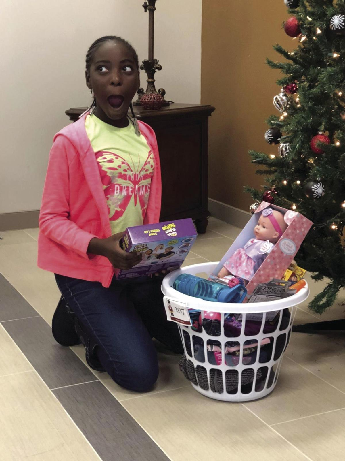 One of the children was excited about her basket of gifts at Y Christmas last year.