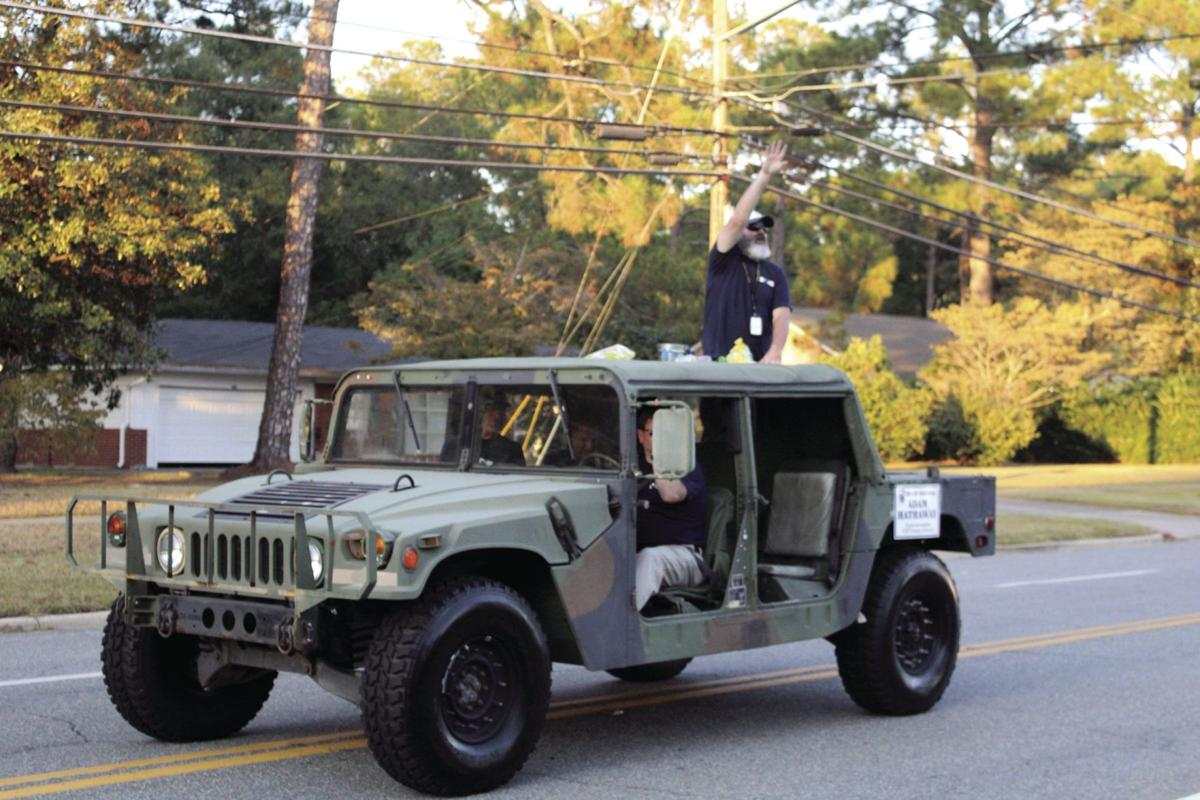 Superintendent Adam Hathaway rides in a Humvee while throwing candy to the crowds at the Homecoming parade.