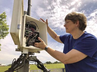 On a sunny day in 2018, Pam Knox checks the data logger at the University of Georgia weather station on the Durham Horticulture Farm in Watkinsville.