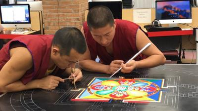 Monks creating sand mandala at university