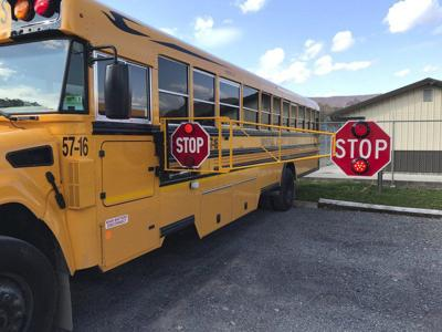 Extended stop sign arm installed on school bus eliminates passing