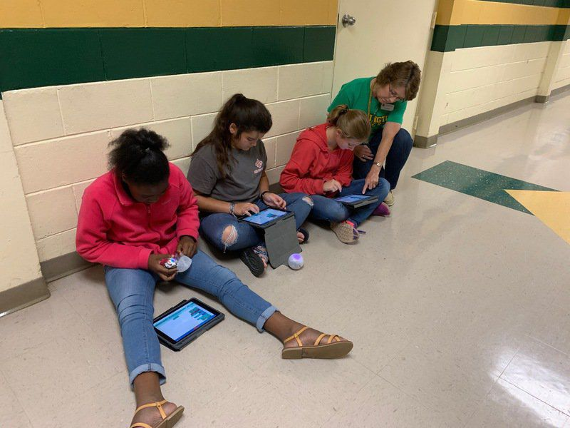 Robots getting the code from middle schoolers