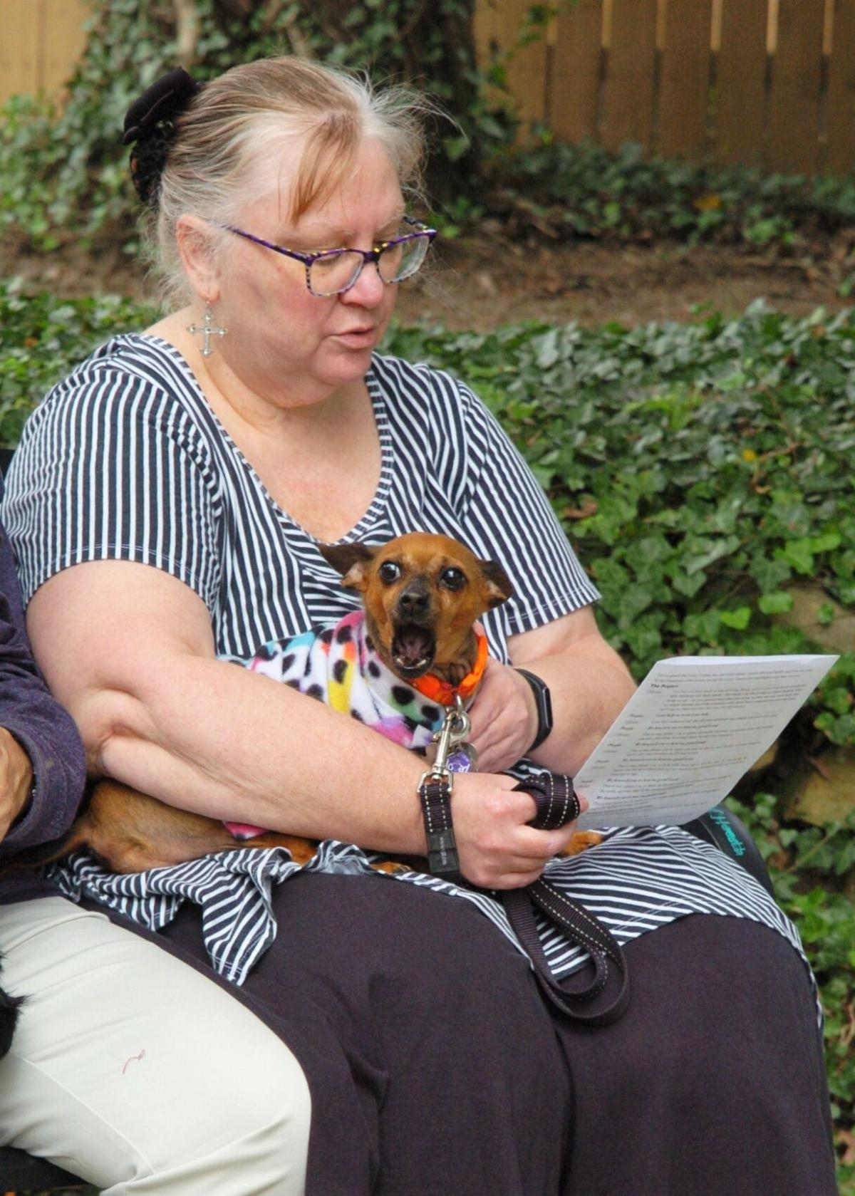 Vicki Iber reads along during the Blessing of the Animals