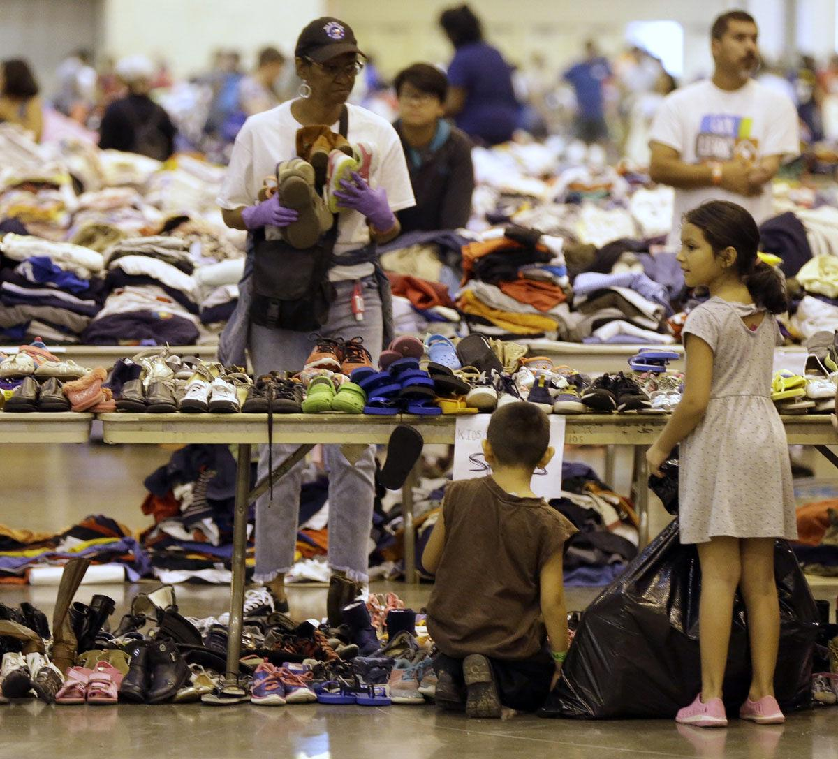 Harvey flood evacuee children look through donated shoes at a shelter setup inside NRG Center Wednesday in Houston.