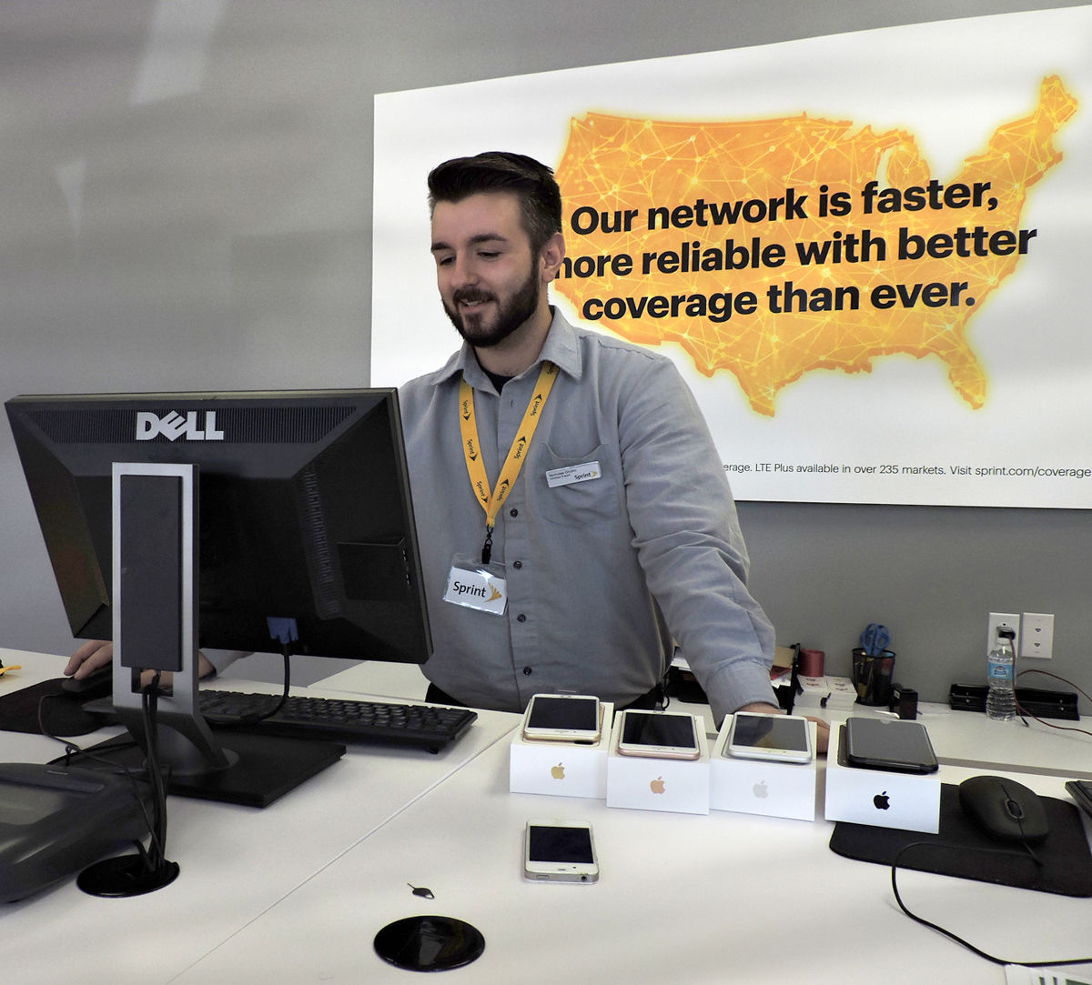 Sprint Store Associate Nick Grubic Looks Up Information To Help A Customer  With Phone Issues.