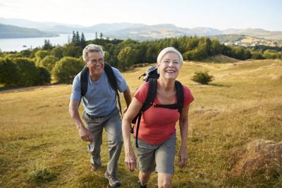 Portrait Of Senior Couple Climbing Hill On Hike Through Countryside In Lake District UK Together