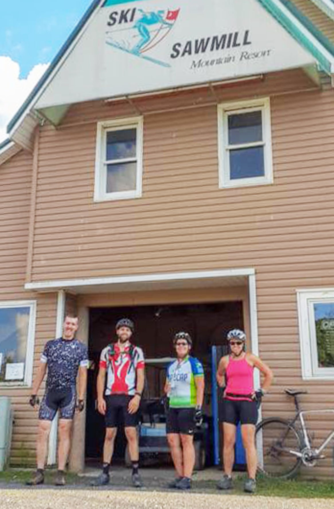 Bicyclists pose for photo outside of Ski Sawmill