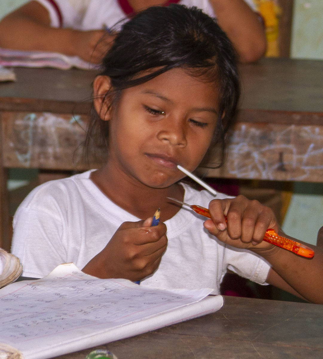 Girl sharpens pencil with blade