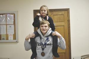 <p><strong>Jenna Greer, 7, holds up her second-place medal from the 50 pound weight class of the 8 and under girls division of the Pennsylvania Junior Wrestling state tournament last weekend. She sits on the shoulders of her cousin Hunter Thompson, the  all-time win leader of the Titusville High School wrestling program who also medaled at states this year.</strong></p><p><strong> </strong></p>
