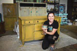 <p>Sonia Miller poses with a can of Junk Monkey paint in her studio located in Titusville. Miller, who recently moved into the area, is the co-founder of the company, and has attracted international attention through her online videos showing her painting works and teaching others how they can do the same.</p>