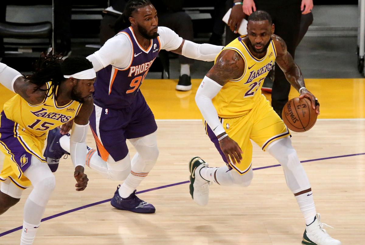The Los Angeles Lakers' LeBron James, right, moves the ball against the Phoenix Suns during the first quarter in Game 6 of the Western Conference first-round series at Staples Center on Thursday, June 3, 2021 in Los Angeles.