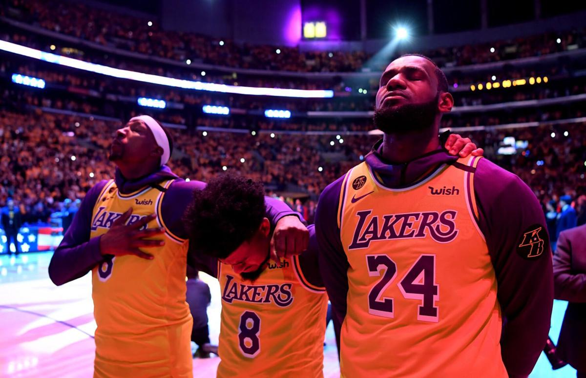 From left, the Los Angeles Lakers' Kentavious Caldwell-Pope, Quinn Cook, and LeBron James close their eyes during a tribute to Kobe Bryant on January 31, 2020, at Staples Center in Los Angeles.