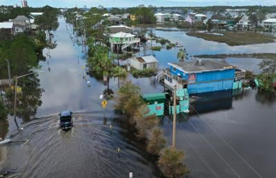 An aerial view from a drone shows a vehicle driving through a flooded street after Hurricane Sally passed through the area on September 17, 2020, in Gulf Shores, Alabama.