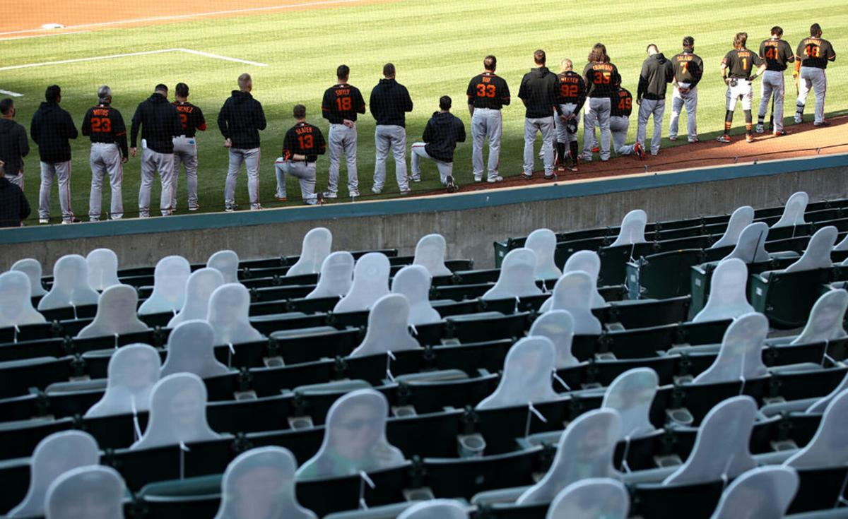 Austin Slater #13 and Jaylin Davis #49 of the San Francisco Giants kneel during the National Anthem before their exhibition game against the Oakland Athletics at Oakland-Alameda County Coliseum on July 20, 2020 in Oakland, California.