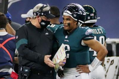 In this file photo, Eagles coach Doug Pederson talks with quarterback Jalen Hurts during a game against the Dallas Cowboys on Dec. 27th, 2020 at AT&T Stadium in Arlington, Texas.