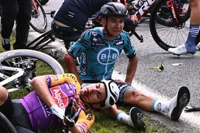 Team B&B KTM's Bryan Coquard of France, right, and a Team Alpecin Fenix' rider lie on the ground after crashing during the first stage of the 108th edition of the Tour de France cycling race, 197 km between Brest and Landerneau, on Saturday, June 26, 2021.