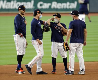 The Houston Astros' Jose Altuve, second from right, bumps elbows with Aledmys Diaz as Alex Bregman and Carlos Correa look on before an intrasquad game at Minute Maid Park in Houston on July 17, 2020.