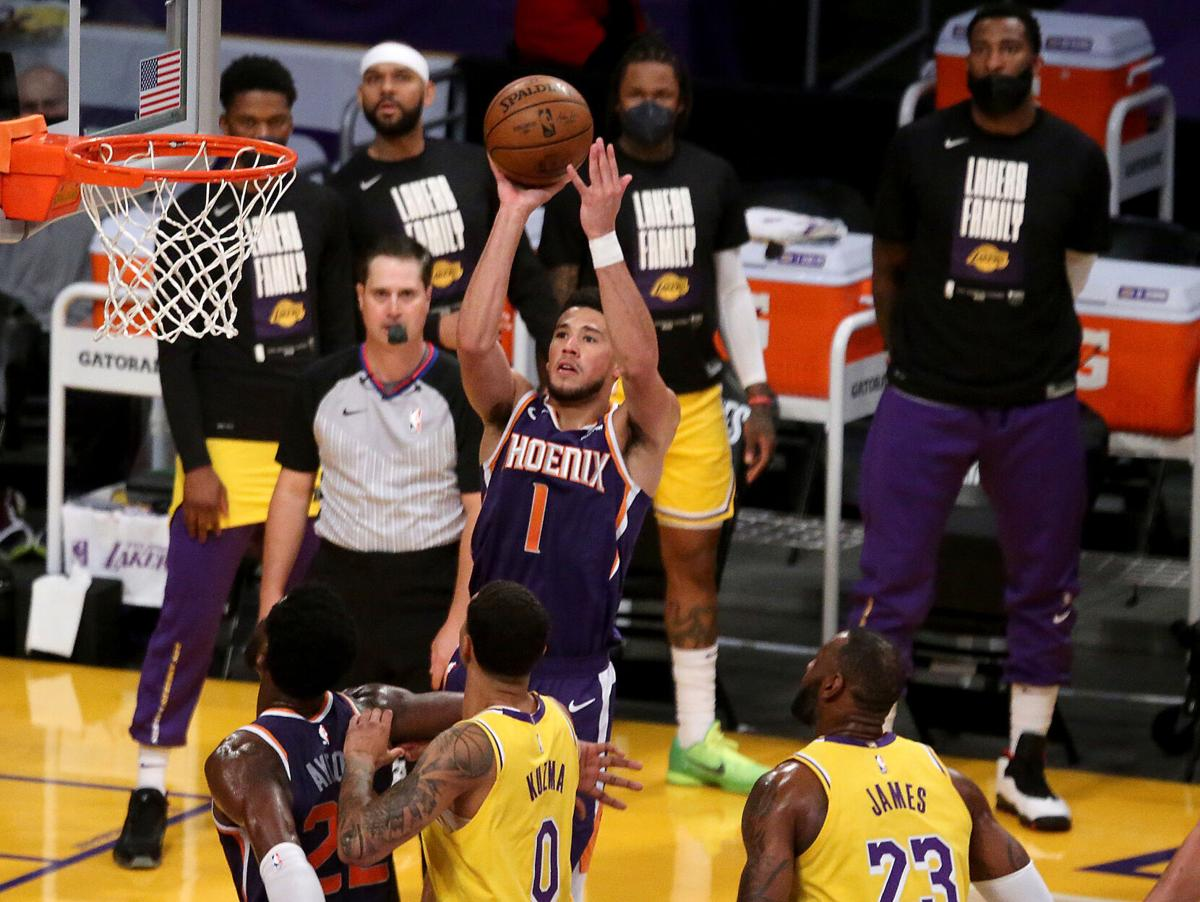 The Phoenix Suns' Devin Booker shoots and scores against the Los Angeles Lakers during the first quarter in Game 6 of the Western Conference first-round series at Staples Center on Thursday, June 3, 2021 in Los Angeles.