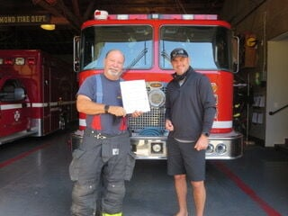 Photo of Brian Webber accepting an envelope of checks from Matt Schelegle, Alameda Fire Captain and Brook Lomond resident. — contributed