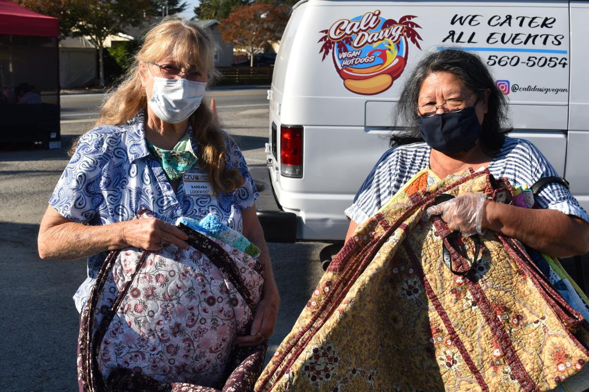 STITCHING TOGETHER COMMUNITY Barbara Lockwood, drive organizer, helps CZU August Lightning Complex survivor Darlene out to her car with her new quilts. — Katie Evans/The Press Banner