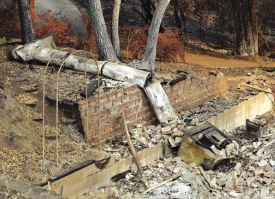 STAY ALERT A wood stove and chimney collapsed and surrounding woodlands were scorched at this Boulder Creek home during the CZU August Lightning Complex fires. Officials are now fearing debris flows as seasonal rains start up. — Tarmo Hannula/The Press Banner file