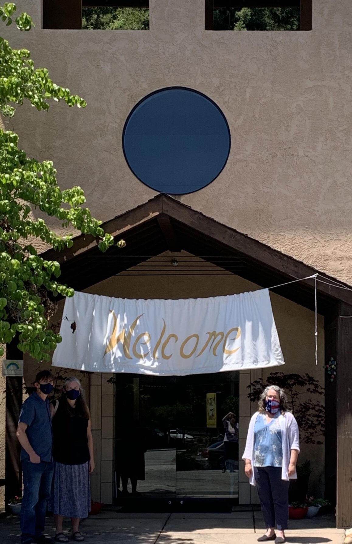 n front of the Welcome sign with Senior Warden Marcus Granger-Jones, and Vestry member Vicky Granger-Jones.